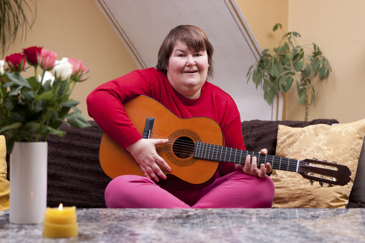 Mentally disbaled woman playing guitar